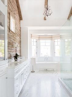 White Bathroom. White Bathroom with reclaimed wood accent wall, ceiling beams, vaulted ceiling, French chandelier, marble floor tiling, bay windows and freestanding bathtub. #Bathroom Blackband Design.