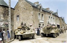 """M8 armored cars of the 705th Tank Destroyer Battalion, Recon 'B"""" Company pass through Miniac-Morvan in Brittany 3-4th August 1944."""
