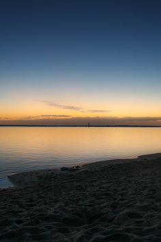Body of Water Near Beige Sand Under Blue and White Sky at Sunset