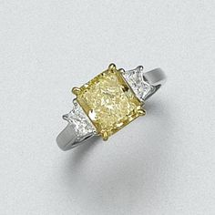 FANCY INTENSE YELLOW DIAMOND RING, CARTIER Set with a cut-cornered rectangular modified brilliant-cut diamond of fancy intense yellow color weighing 2.81 carats, flanked by 2 calf's-head-cut diamonds, mounted in platinum and 18 karat gold, size 6,  signed Cartier.