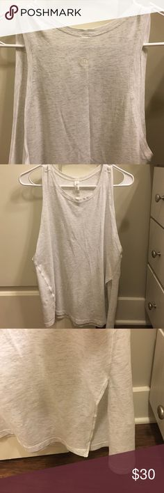 Lulu Lemon Tank I absolutely love this tank! It is a beautiful light gray, it drops low on the sides, and it has a side insert. Looks great if you just leave it down or if you want to tie it up. lululemon athletica Tops Muscle Tees