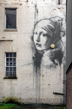 The new Banksy depicting the painting 'Girl with a Pearl Earring' by Dutch painter Johannes Vermeer is seen on a wall in Bristol Harbourside, England on Oct. 20, 2014.