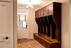 Built-in lockers with open hooks, bench and drawers in mud room - brick flooring and light fixture for garage entry - Farinelli Construction