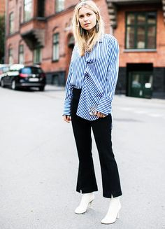 Pernille Teisbaek punctuates a relatively simple ensemble- a blue striped shirt and black trousers from By Malene Birger- with dazzling earrings from the same Danish label and some white Vétements boots.