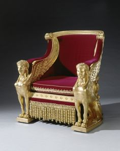 Located 2015 in the Throne Room of Buckingham Palace, London, UK. Gilt & ornate council chair of red velvet, 1 of a pair, made by Tatham, Bailey & Sanders in 1812. Backs shaped like Roman chariots are solid to the ground & elaborately carved, as is the whole. Padded velvet armrests are supported on the wings & heads of 2 carved sphinxes on either side of each chair. Purchased by George IV (1762-1830) UK, Uncle of Queen Victoria (1819-1901) UK.