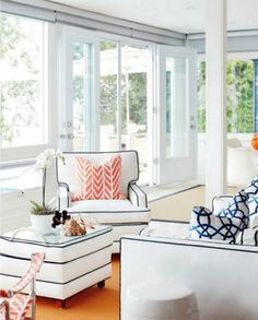 Love the clean lines, piping on the couches, and the orange and navy color combo on the pillows.