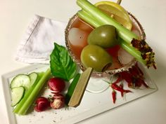 An Herbal Bloody Mary with Basil, Sage, URBANHERBAL's Spicy Mexican Savory Salt, Tito's Vodka, Clamato Juice and garnished with Lemon, celery, olives