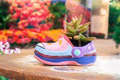 Dieses Kind Schuh mit brillanten Pastell-Farben verwendet, als Pflanzer in ein einzigartiges Werk Mittelpunkt nimmt, als es bequem allein in seiner Einsamkeit sitzt gemalt.