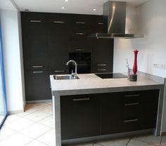 Aménagement coin cuisine ouverte avec ilot central intégrant placards + plaque induction et hotte + évier , et mur de rangement.