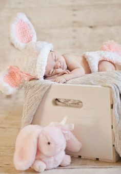 Newborn photography pose with adorable bunny hat.