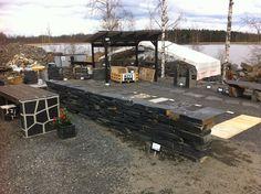 Lohkokivimuuri ja mallipolkuja Viinijärven Kiven myyntinäyttelyssä. Taustalla olevassa katoksessa on laaja valikoima sisustuskivilevyjä valmiiksi saumattuna.