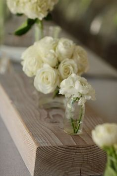 All-white florals in clear containers on pieces of whitewashed wood | Joanna and Michael's wedding by Steven Moore Designs, featured on Elizabeth Anne Designs