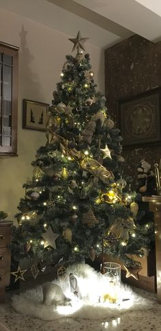 """My Christmas tree with golden and wood ornaments. Merry Christmas!  Mi árbol de Navidad de este año, con adornos de madera y dorados. En la parte de abajo hay un oso polar, un Papa Noel y un jarrón en el que se lee """"let it snow"""" cuyo interior he rellenado con unas velas doradas, espumillón y luces. Feliz Navidad!"""