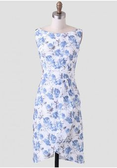 <p>Perfected with a retro-inspired feel, this fitted white dress features a blue and gray floral print and faux wrap tulip skirt. Finished with a boat neckline and pleating at the waist, this ladylike dress can be styled with pumps and a handbag for quintessential Ruchette ensemble. Hidden back zipper closure. Unlined but opaque. By Queen Of Heartz.</p> <p>100% Cotton<br /> Imported<br /> 32