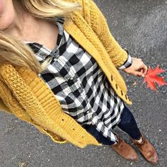 Yellow cardigan over black and white checked shirt with black jeans.