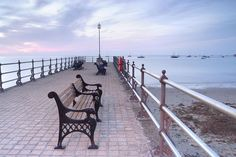 Small jetty and empty bench seats, Swanage bay at dawn, dorset,england,uk