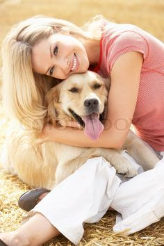 Stock Bild von 'Frau sitzt mit Hund auf Strohballen in abgeernteten Feld'