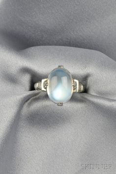 14kt White Gold and Moonstone Ring, Marcus & Co., set with a cabochon moonstone measuring approx. 14.30 x 10.20 x 6.40 mm, size 7, signed. Art Deco or Art Deco style
