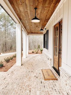 Everything about this porch is absolutely on point - from the lighter finish on the brick to the wood finish for the bottom of the roof. Beautiful! #HomeDesign #ModernFarmhouse #Farmhouse #FrontPorch #HomeInspiration #FrontPorchViews #BrickPatio #OutdoorSpace #OutdoorSpaceInspiration