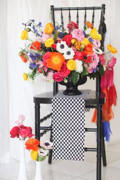Brightly colored tassels on chair matches floral arrangement. Source:  Michelle Kim Photography. #tassels #chairdecor #centerpiece