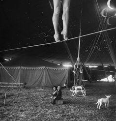 Nina Leen, Two small children watching a circus performer practicing on a tightrope, Sarasota, Florida, USA, March 1949.