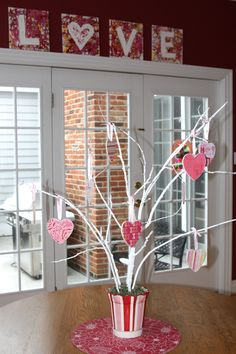 Painted a tree branch white and then hung little wooden hearts with valentine's paper.