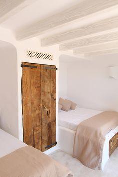 Dormitorio rústico y mínimo al tiempo. Armario de madera reciclada. Camas de obra. Interiorismo blanco.