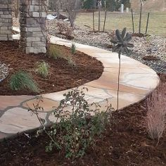 A curvy, natural stone pathway leads you to the back of this house www.earthscaped.com
