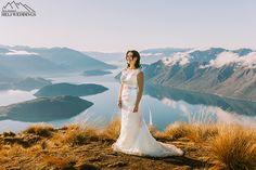 bride stands on Coromandel peak for wedding photos. Heli Wedding Wanaka New Zealand
