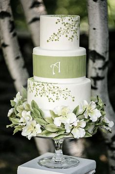 This white wedding cake with green floral designs is a beautiful choice for a spring wedding celebration.