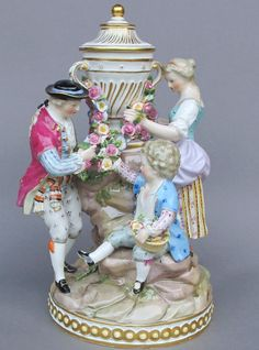 Meissen Model: D 92        Description: Boys And Girl With Garlands   Modeled By: Michel Victor Acier ca. 1772   Mark: D 92       Painter Number:    Height: 9.5 in - 24.1 cm  Notes: Urn Has Removable Lid