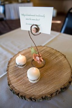 Here's a wonderful DIY non-floral centerpiece idea from Katie Sue's wedding — a log-sliced wooden base, with two wrapped candles and trivia about wedding traditions held aloft for guests ponder: