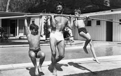 Pole-r opposites? Iron man Douglas lifts his sons, Joel (L) and Michael (R) using a full-length pole near the edge of a swimming pool, circa 1955. (Getty Images)