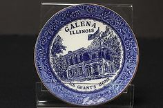 """6 1/8"""" diameter souvenir plate. Features blue and white depiction on front 'Galena Illinois U.S. Grant's Home.' Unmarked by the maker. Has an adhered hanger on back. Wear on the gilt rimming and crazi"""