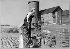 Miss Mildred Saums of Three Bridges, New Jersey helps her brother catch up with his spring work by running the John Deere tractor for him after her work as chief clerk in the Flemington Auction Market Cooperative Association in May 1942.