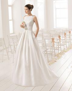 Vestido de novia clásico de costura de piqué con escote barco y espalda en pico joya con pedrería frost, en color natural.