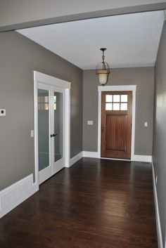 Gray paint, dark plank floors, white trim, industrial light. Frosted french doors.  Bruder House - C&M Properties and Construction. www.candmhomebuilders.com Eau Claire, Wisconsin