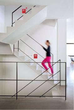 Escalier en béton brut peint, équipé d'un garde-corps minimaliste en fer plat.