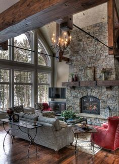 Rustic Living Room with stone fireplace, Chandelier, Exposed beam, Cliffstone Stone Veneer, Hardwood floors, High ceiling