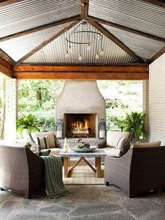 COCOCOZY: OUTDOOR LIVING ROOM - WICKER  BRICK - GET THE LOOK visit the blog to see more.  Love this steel roof on this covered patio with fireplace and white brick wall!  Very cozy