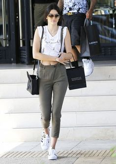 Kendall Jenner wears a distressed white cropped tank, olive green trousers, adidas Superstar sneakers, and mini black Céline bag