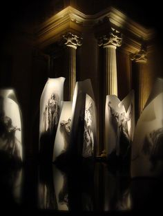 """""""Extases"""" exhibition, 2011. Ernest Pignon-Ernest (born 1942). Musée d'art et d'histoire de Saint-Denis, formerly a Carmelite chapel. Seven life-size drawings of mystics - Marie-Madeleine, Hildegarde de Bingen, Angela of Foligno, Catherine of Siena, Teresa of Avila, Marie de l'Incarnation, Madame Guyon. Drawings in black chalk and charcoal on white paper, pasted on aluminum plates. The plates stand on black tile depicting water that reflects  these """"sculptures"""" and the columns of the chapel."""