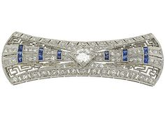 The key to classic style is shimmer paired with a pop of color with this fabulous vintage Art Deco diamond and sapphire brooch. Crafted in icy platinum, this Deco delight features the frosty twinkle of diamonds paired with bands of sapphires around a central diamond. A Greek key design adds a textural accent to the luminescent brooch.