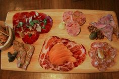 "The butcher's board at Bluestem Brasserie, featuring (clockwise from top left) house-cured braesola, pork trotter and olive ""mortadella,"" pig's head terrine, finnochiona, hot coppa topped with apricots, and rustic country pate."