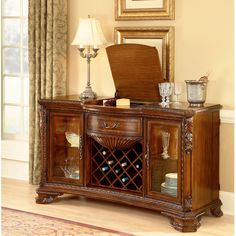 A.R.T. Furniture's Old World Wood Single Drawer Two Door Buffet in Pomegranate by Humble Abode.  Reminiscent of luxurious décor from the Renaissance, this magnificent Buffet is crafted from Cherry wood with Avodire veneers finished in a Vintage Pomegranate stain.  Its center base serves as a wine rack, the top center flips up to serve as a tray and two side display cabinets light up for display.  Exceptionally versatile, while looking incredible, the Old World Buffet is a focal point in any…