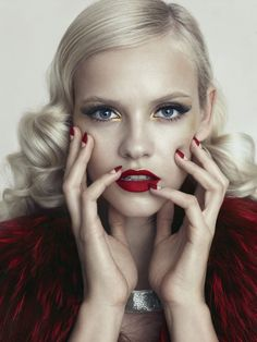 Red lipstick with a gold touch on the cupid bow + eyes with false lashes and gold detail in the inner corner, half moon nails and polished hair with waves