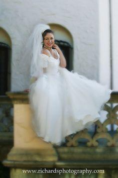 Bridal portraits - bride sitting across ledge at the museum in San Antonio Texas - Richard's Photography