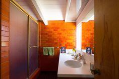 Original, luscious orange tile in this mid century bathroom.