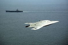 An X-47B Unmanned Combat Air System (UCAS) drone demonstrator flies near the #USNavy aircraft carrier USS George H.W. Bush after its historical launch.