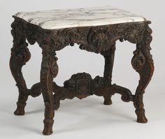 Late 19th century Belgian side table with a serpentine-shaped white and grey marble top over the ornately carved oak frame, the apron with a central mask surrounded by scrolling foliates, raised on cabriole legs ending in hooved feet and joined by an arched stretcher
